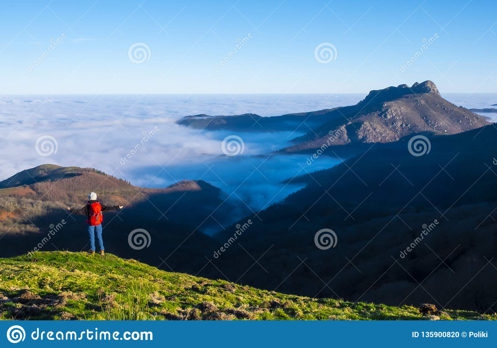 Woman traveler standing on mountain summit over clouds enjoying aerial view. Travel Lifestyle success concept adventure active vac