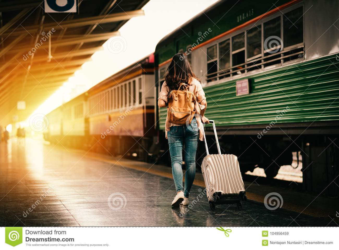 Woman traveler tourist walking with luggage at train station