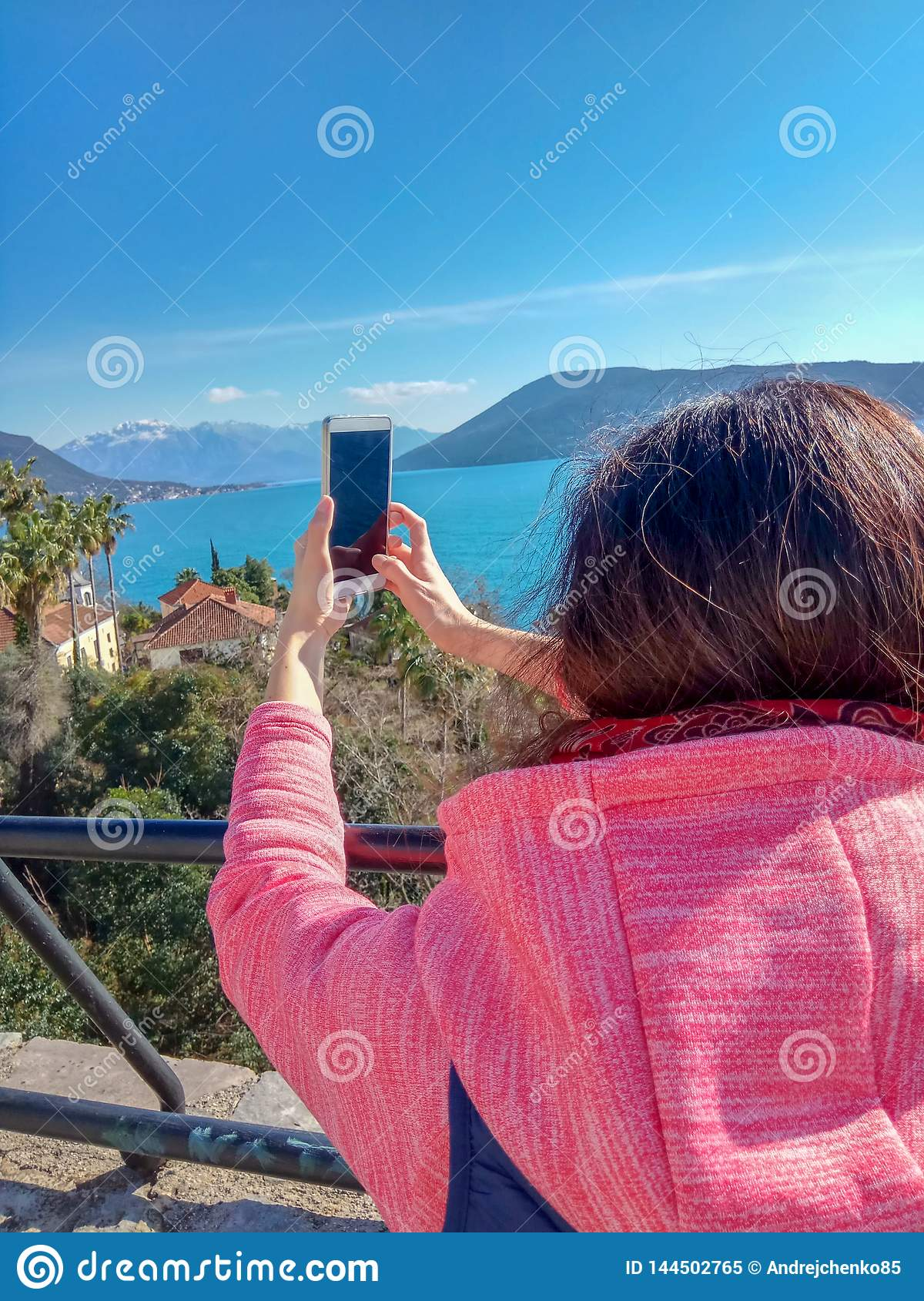Woman traveling use smart phone and touching a mobile screen on mountain and sea.