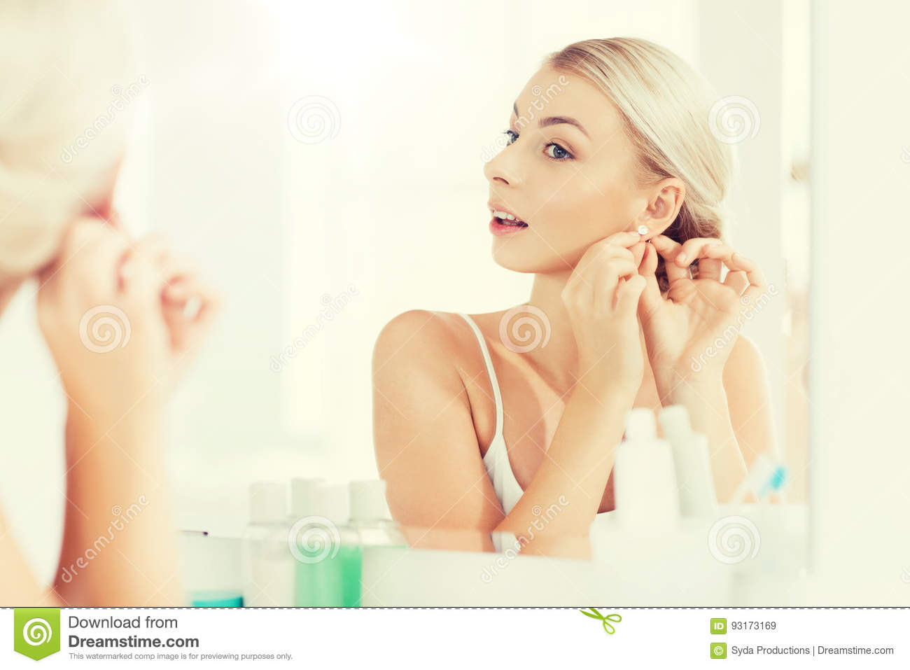 Woman trying on earring looking at bathroom mirror