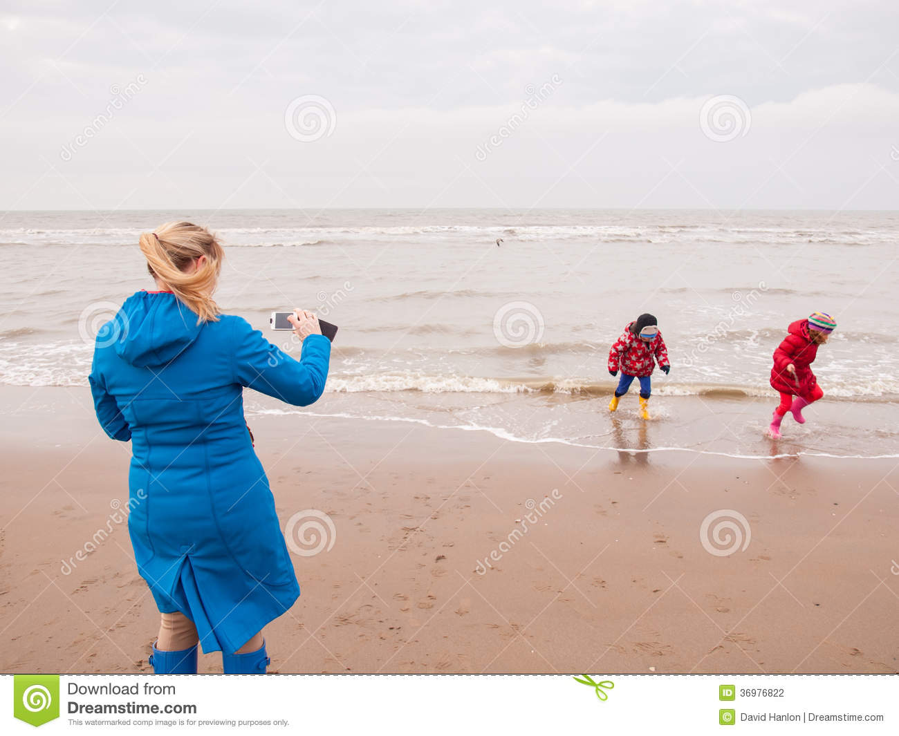 af18f1a4f9 Woman photographing small boy and girl in winter clothing and rubber boots  on a winter beach with a smart phone