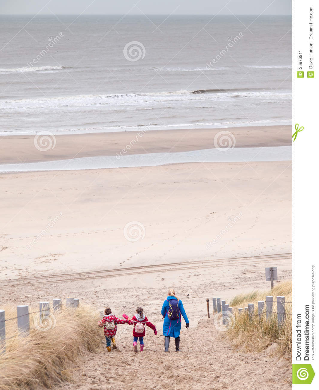 345c7b2c47 Woman with small boy and girl in winter clothing and rubber boots walking  down to a winter beach along a dune path