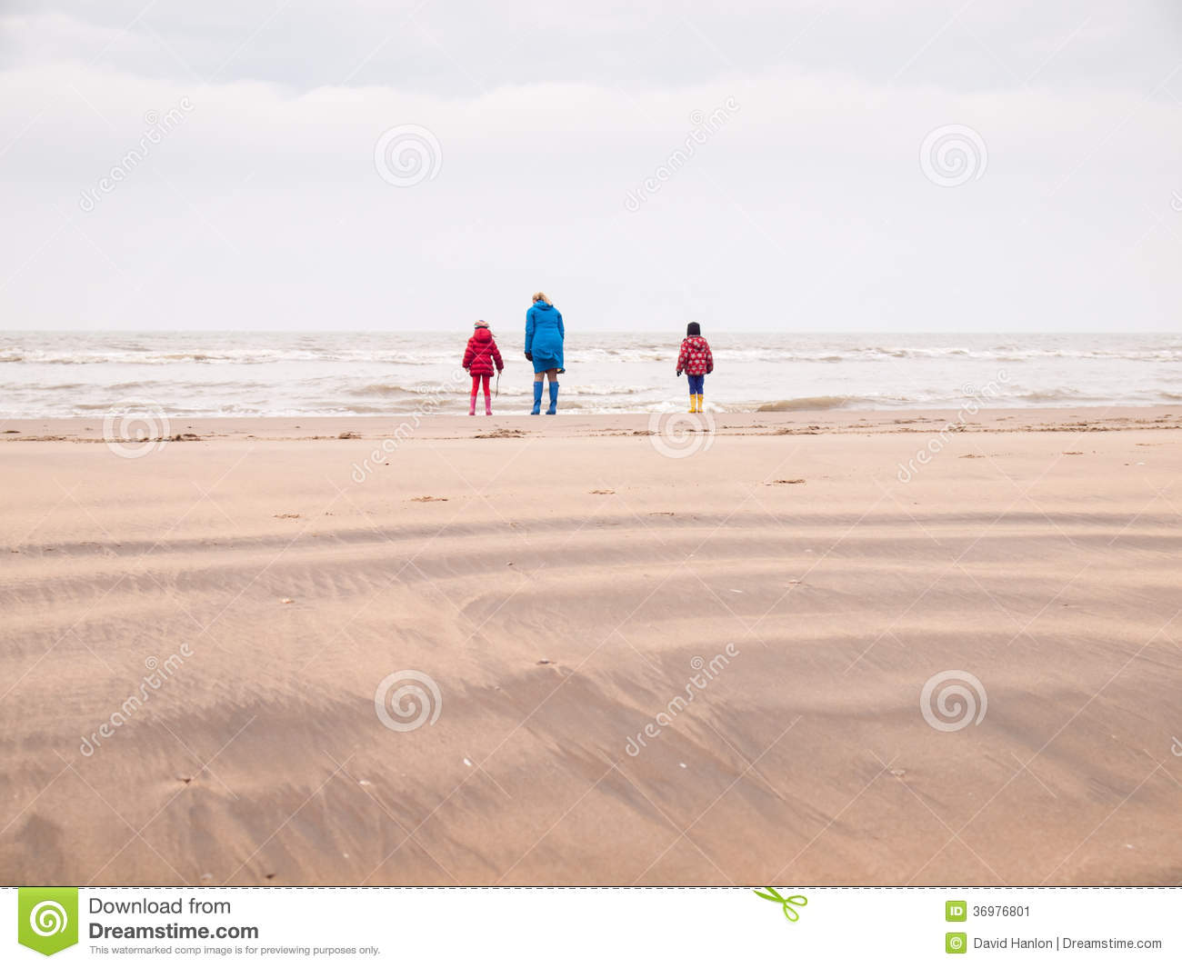 8e374ba58b Woman with small boy and girl in winter clothing and rubber boots on a winter  beach looking out to sea