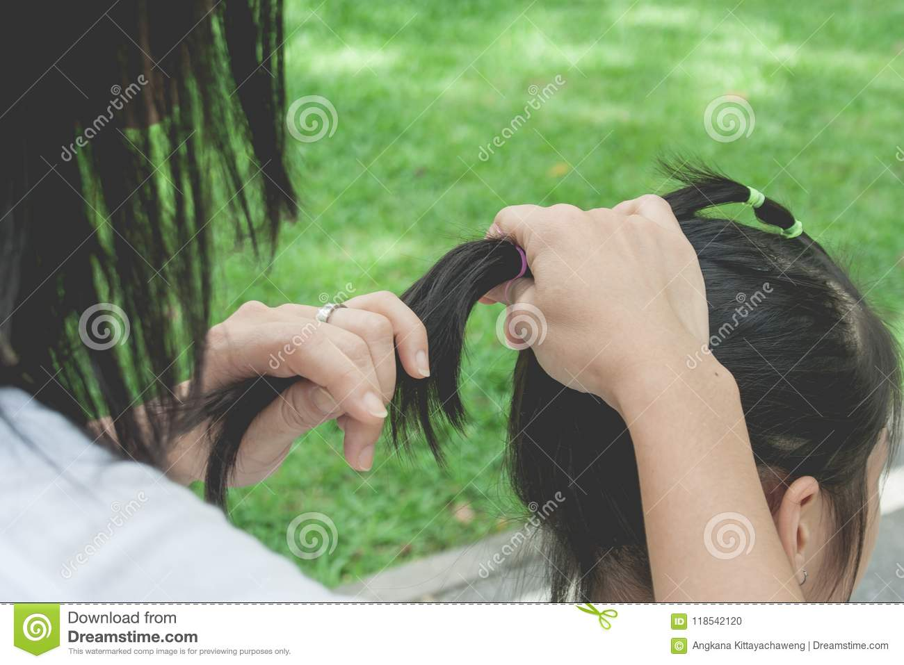 Woman tying black hair of little cute child in ponytail style with elastic band at public park.