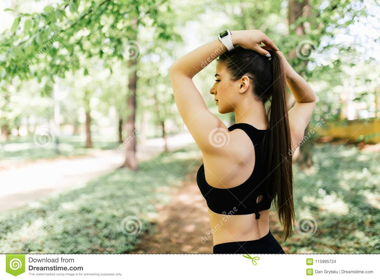 Woman tying hair in ponytail getting ready for exercising in park. Beautiful young sporty woman attaching her long hair in park. S