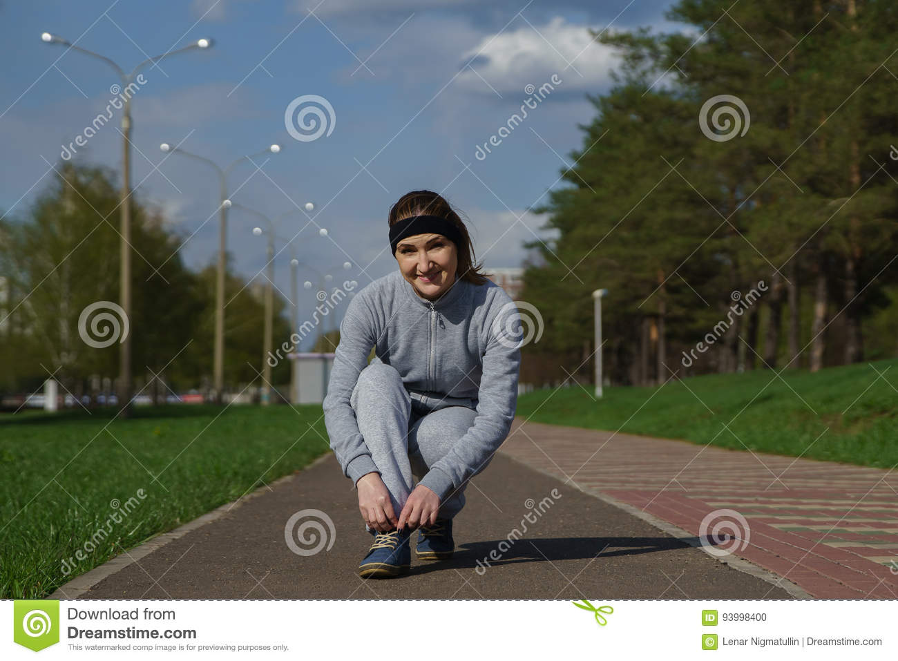 Woman tying shoe laces. Female sport fitness runner getting ready for jogging outdoors on forest path in spring or summer.