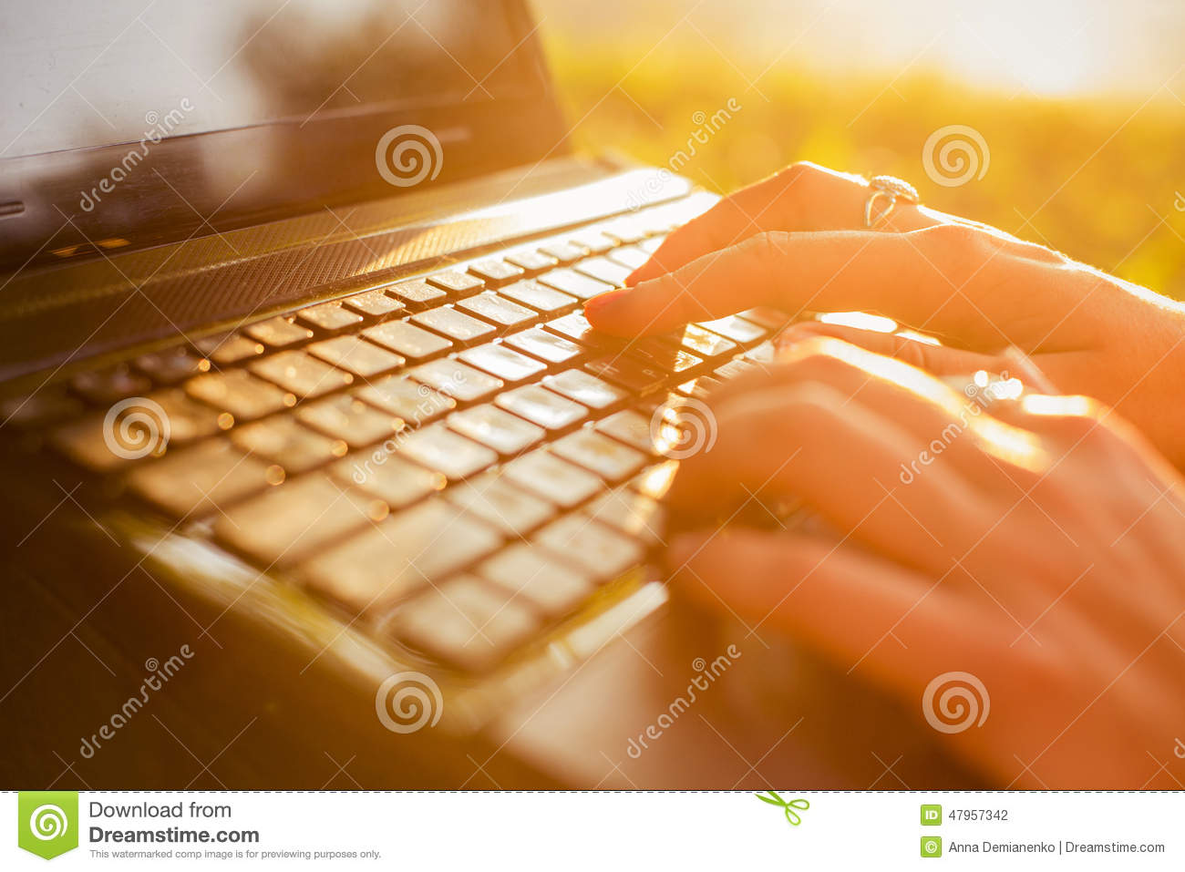 Woman typing on a laptop keyboard in a warm sunny day outdoors.