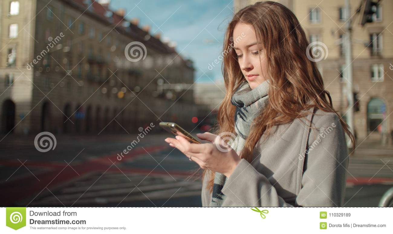Attractive brunette young woman texting on phone while standing on a city street.