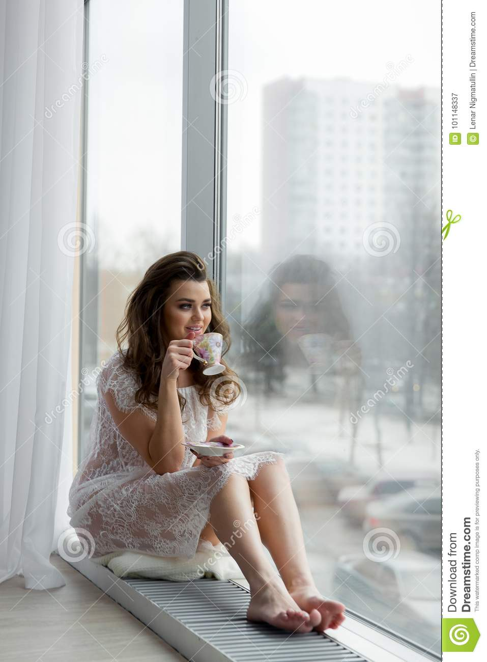 Young Woman In Erotic Transparent Underwear Drinks Coffee On Window Sill Cityscape On Background