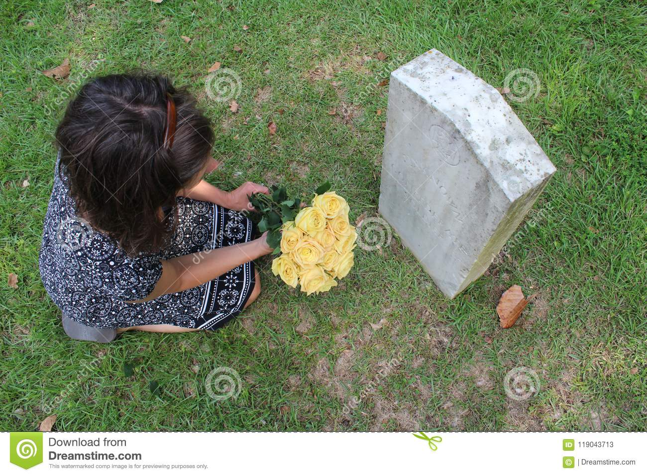 Woman at Unknown soldier`s grave with yellow flowers.