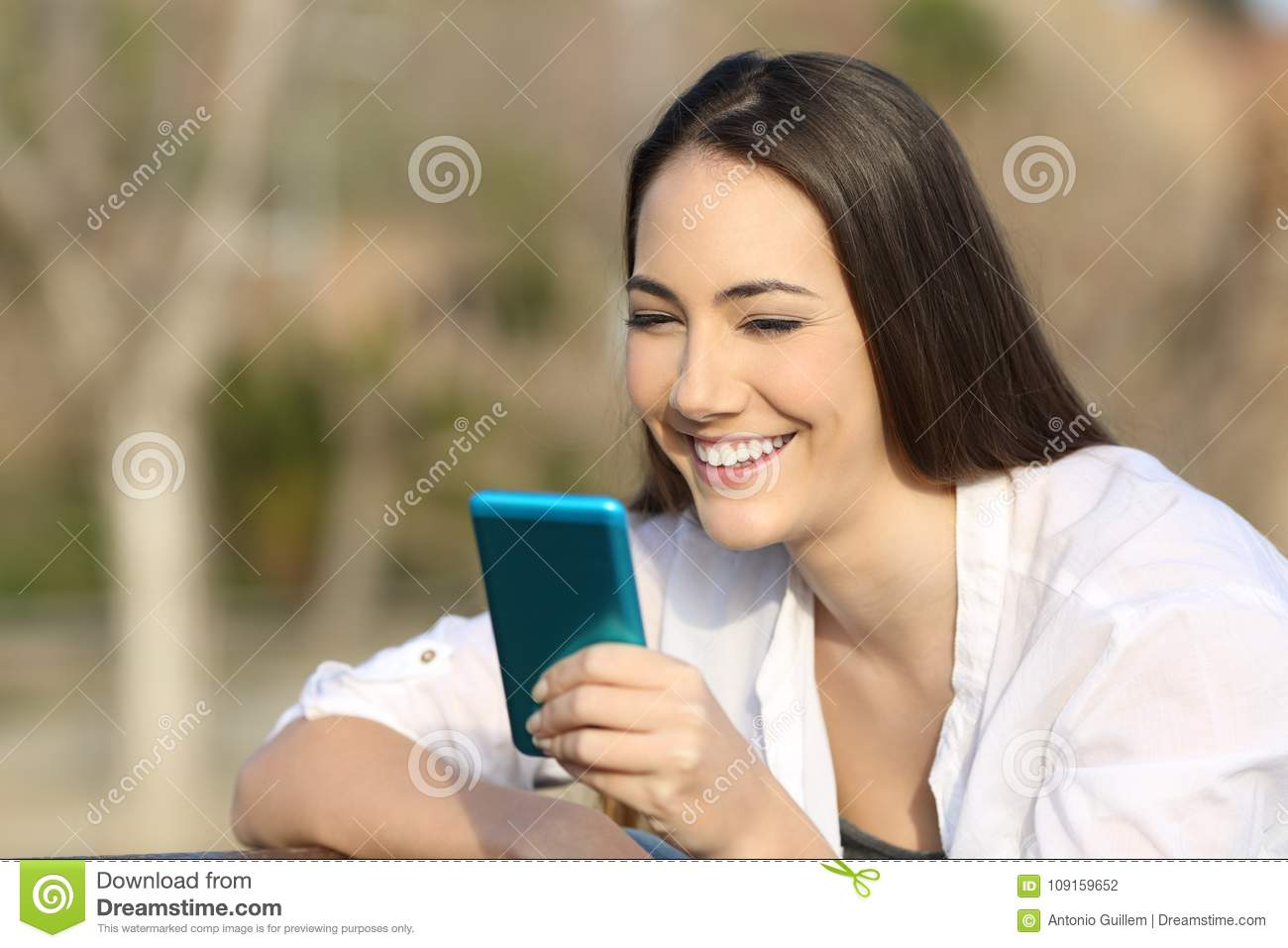 Woman using a blue smart phone outdoors