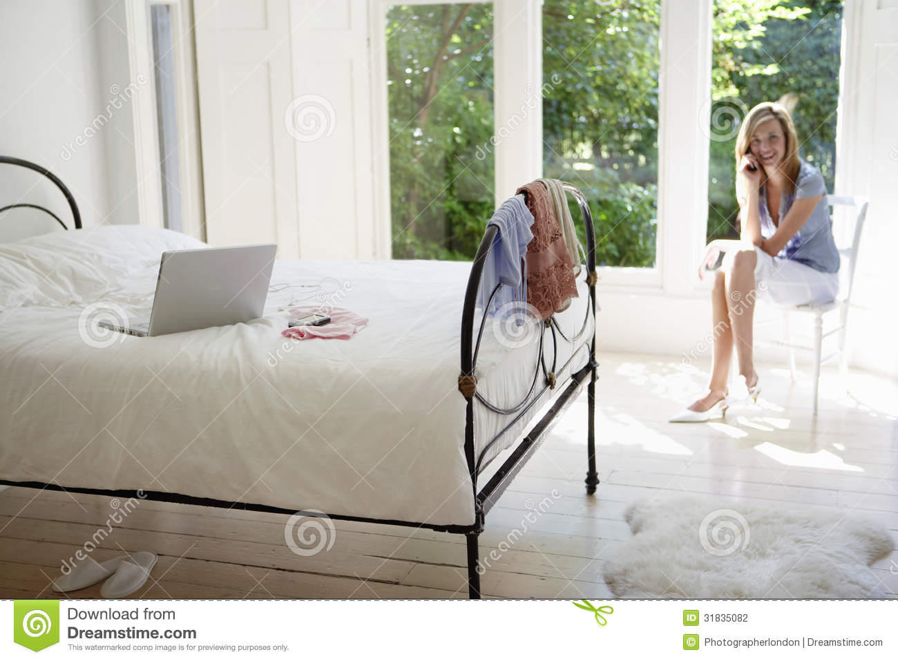 Woman using cell phone with laptop on bed stock for Cell phone bed
