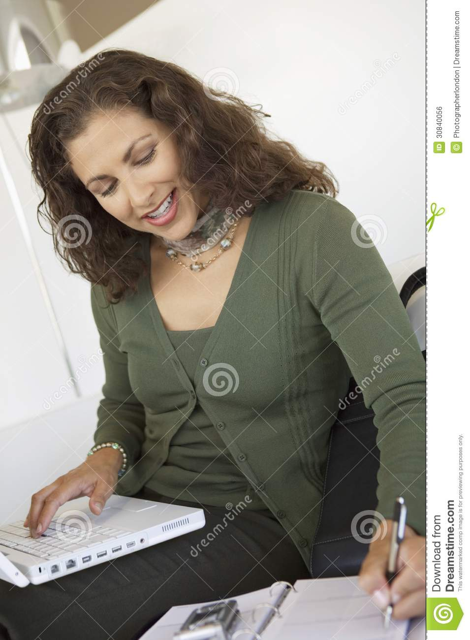 Woman using Cell Phone laptop and Organizer indoors