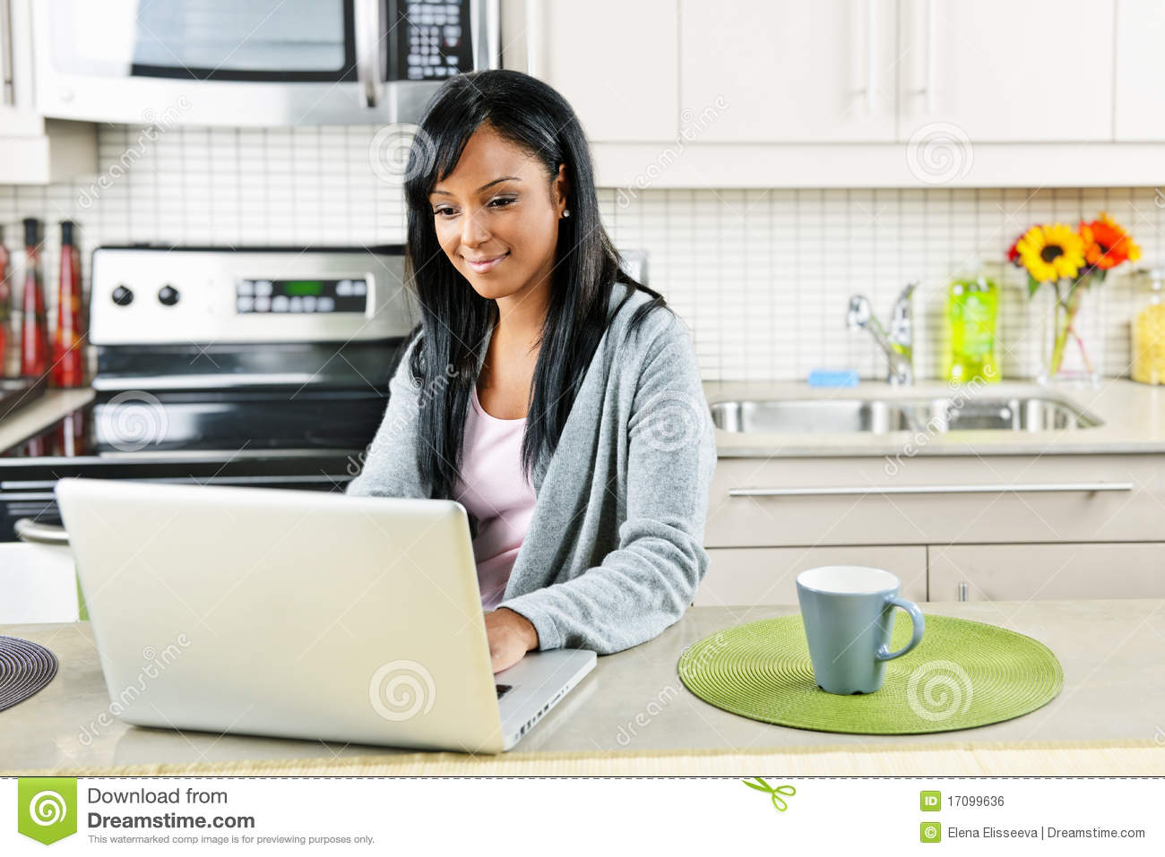 Woman Using Computer In Kitchen Royalty Free Stock Image