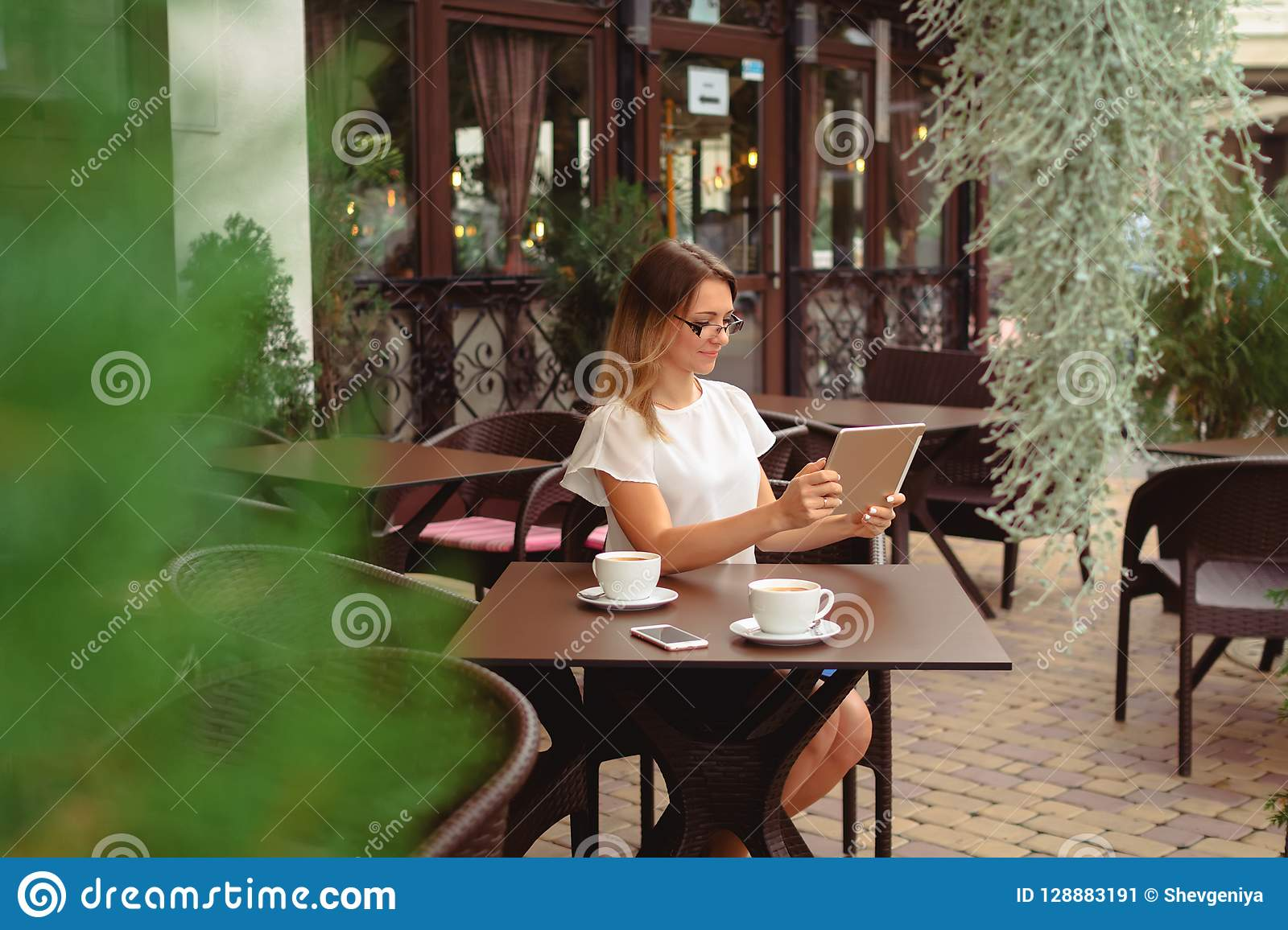 Woman using digital tablet and drinking coffee.