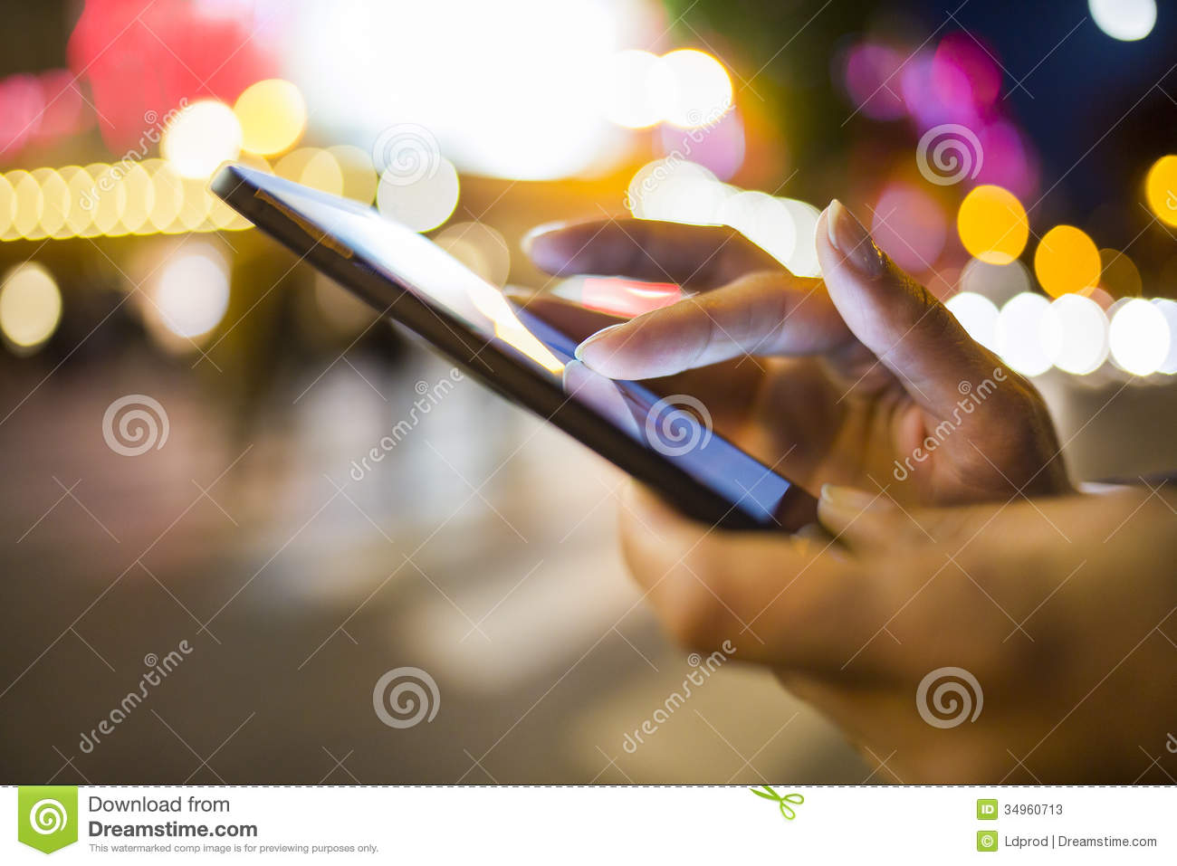 Woman using her Mobile Phone in the street, night light environment