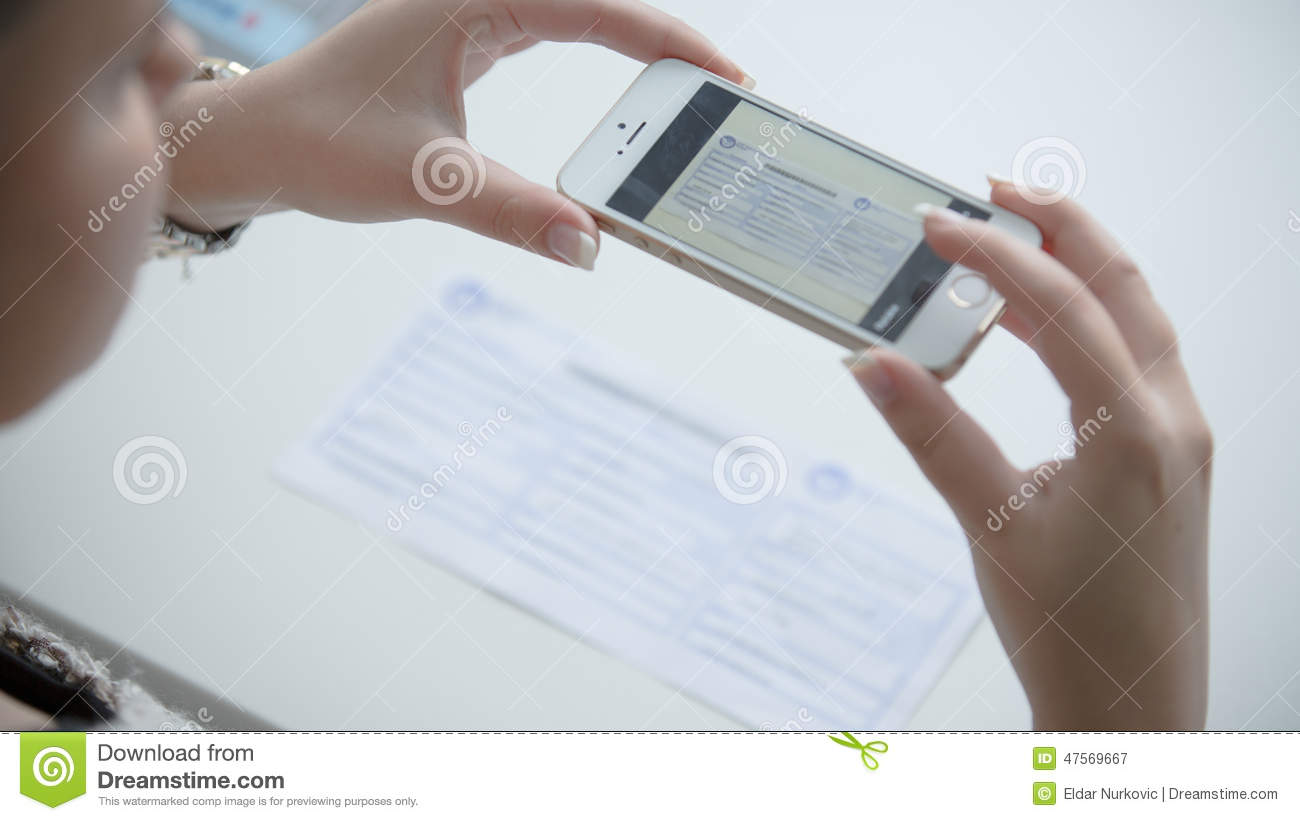 Woman using her phone to take picture of receipt or bill. Online paying bills from comfort of home.Online banking