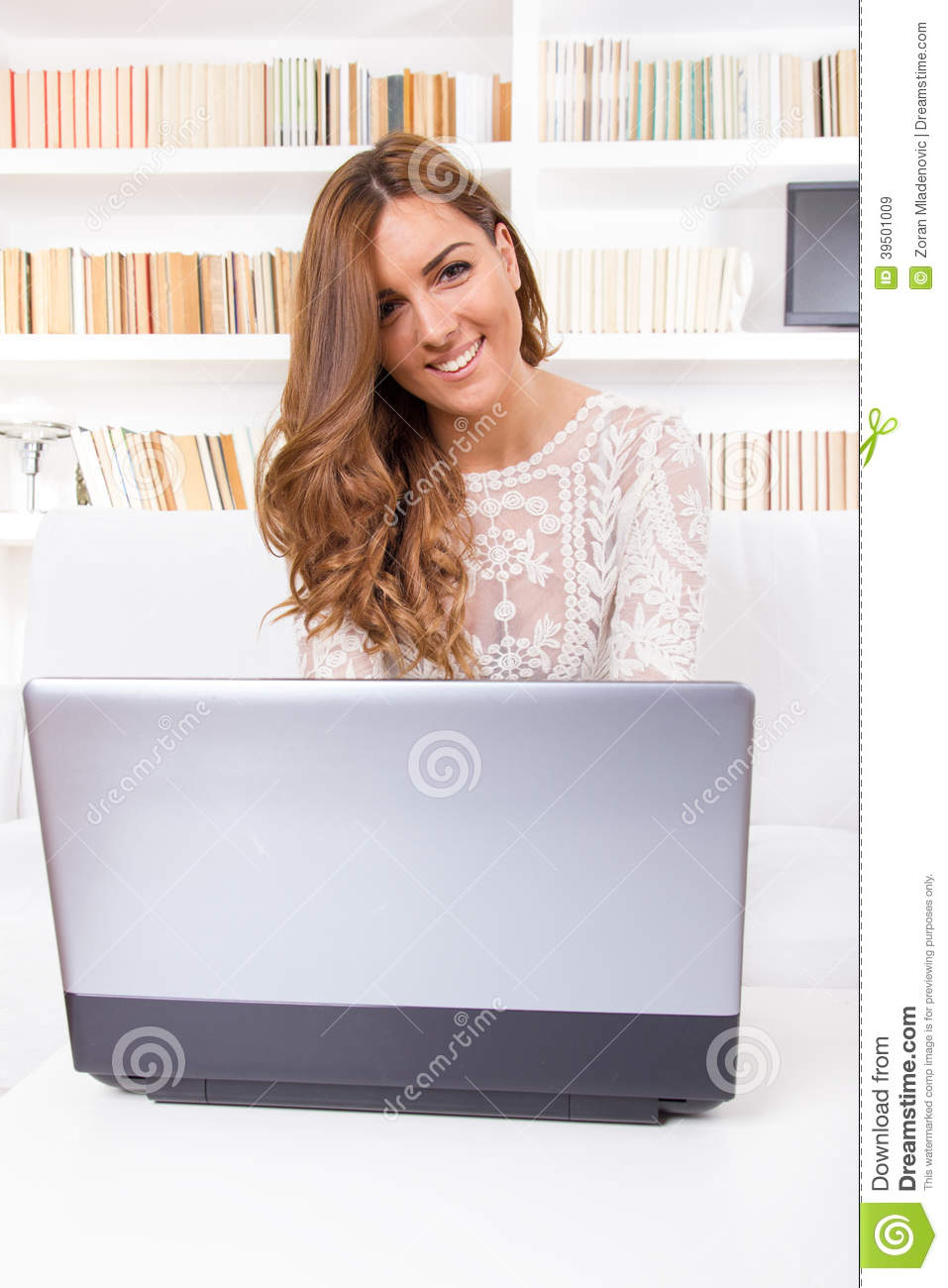 Woman using a laptop computer at home and looking in camera