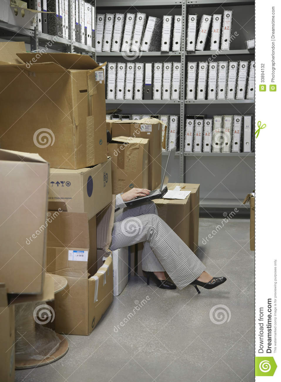 office storage room. Woman Using Laptop In Office Storage Room E