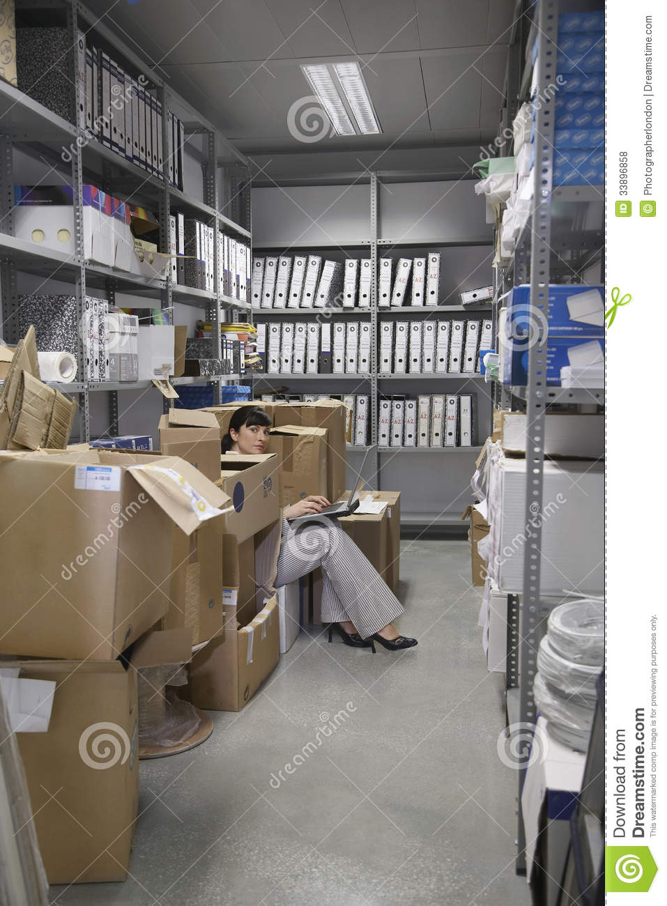 Woman Using Laptop In Office Storage Room Stock Photo