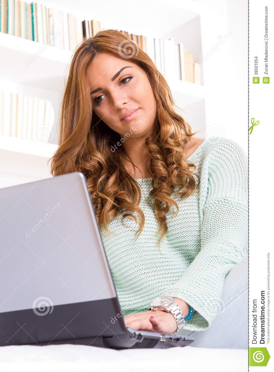 Woman using laptop on sofa in the living room