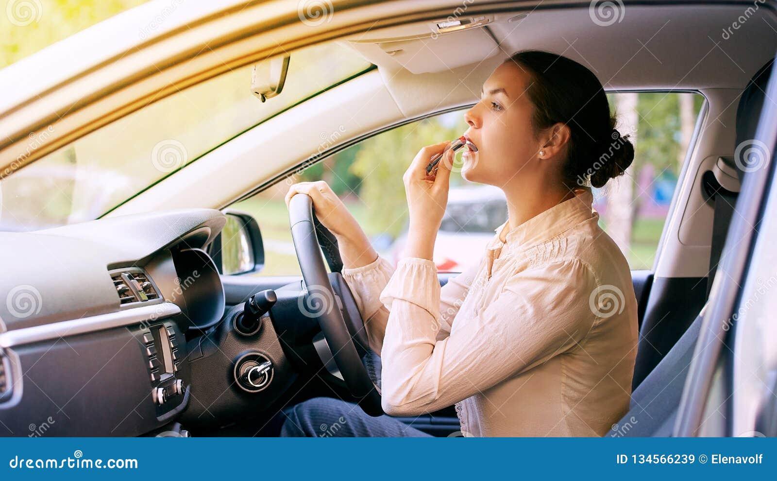 Woman using lipstick inside car. Urban background. Bad busy