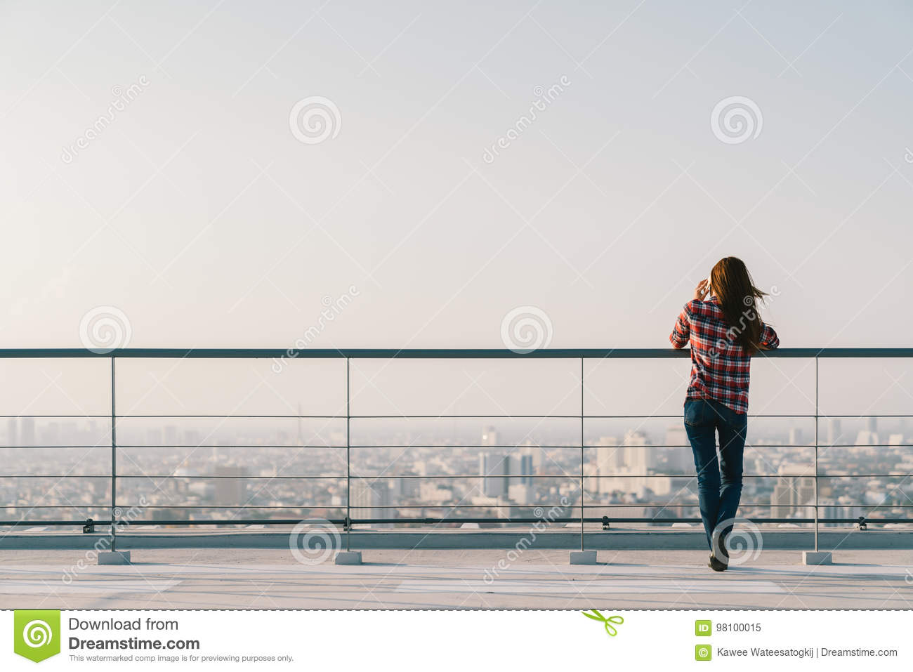 Woman using mobile phone at rooftop during sunset with copy space, communication or lonely people concept