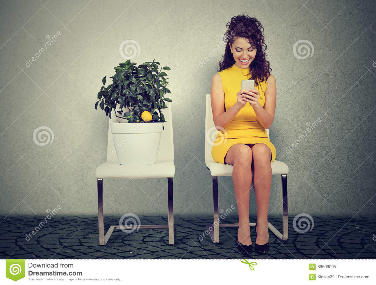 Woman Using Smart Phone Reading An Email Sitting On Chair Next To