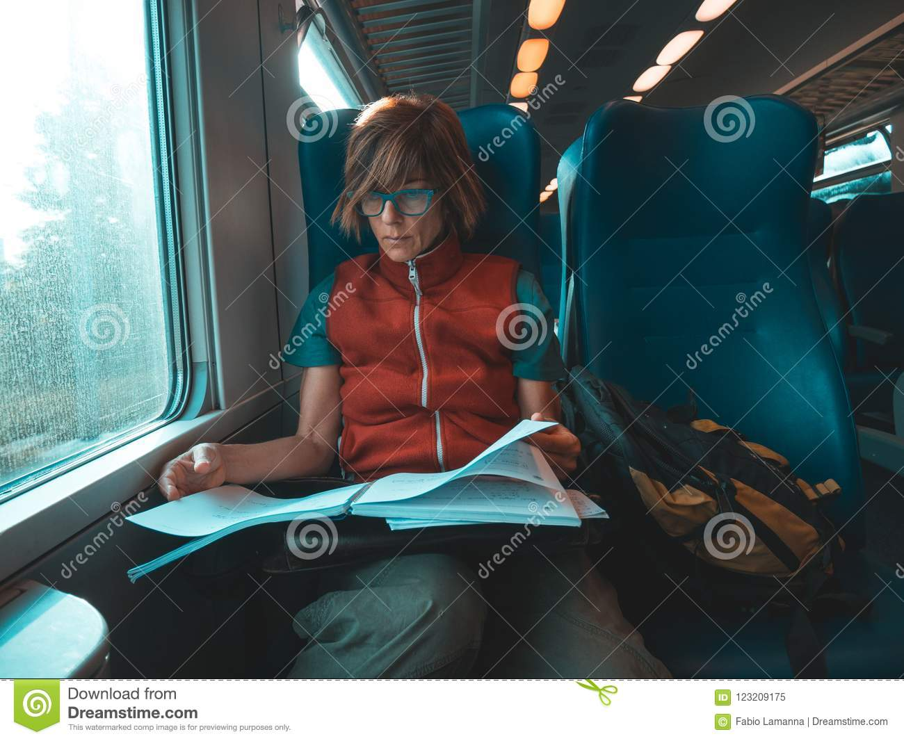 Woman using smart phone sitting traveling by train hand writing on paper. Desaturated cold tone color grading. Working mobility co