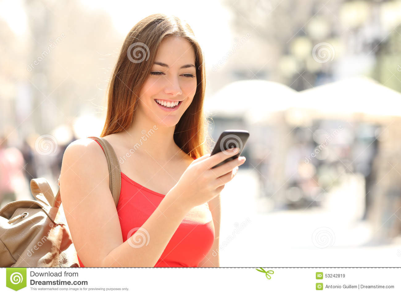 Woman using a smart phone in the street in summer