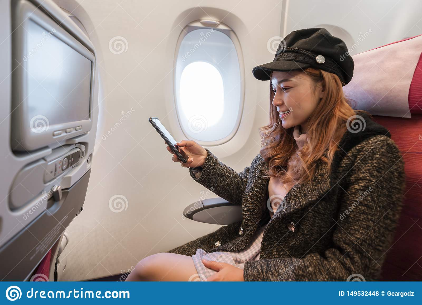 Woman using smartphone in airplane in flight time