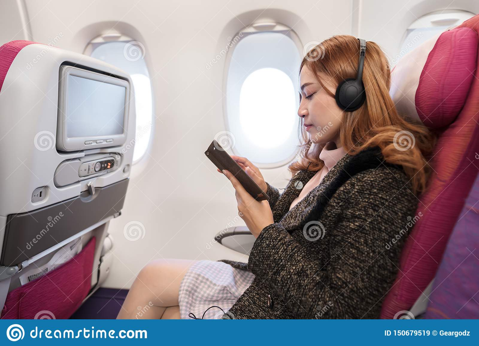 Woman using smartphone and listening to music with headphones on airplane in flight time