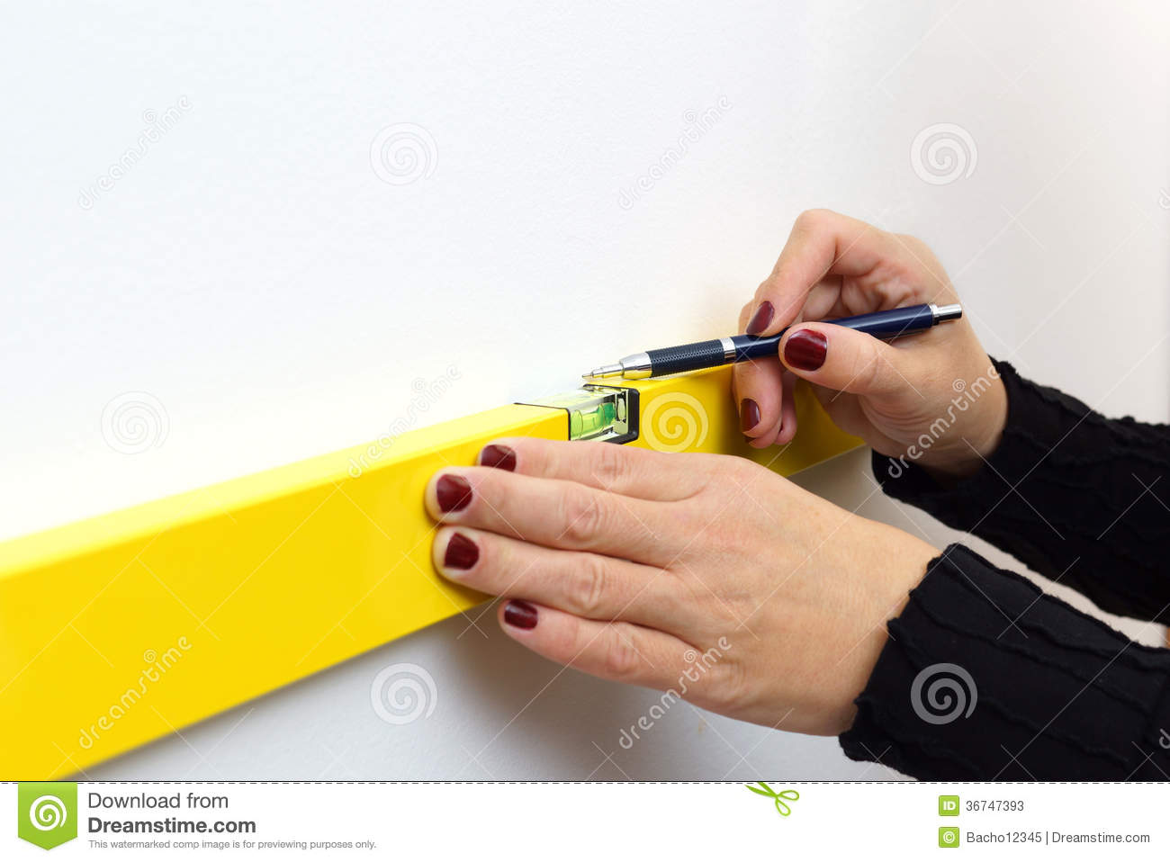 A woman using a spirit level for home work