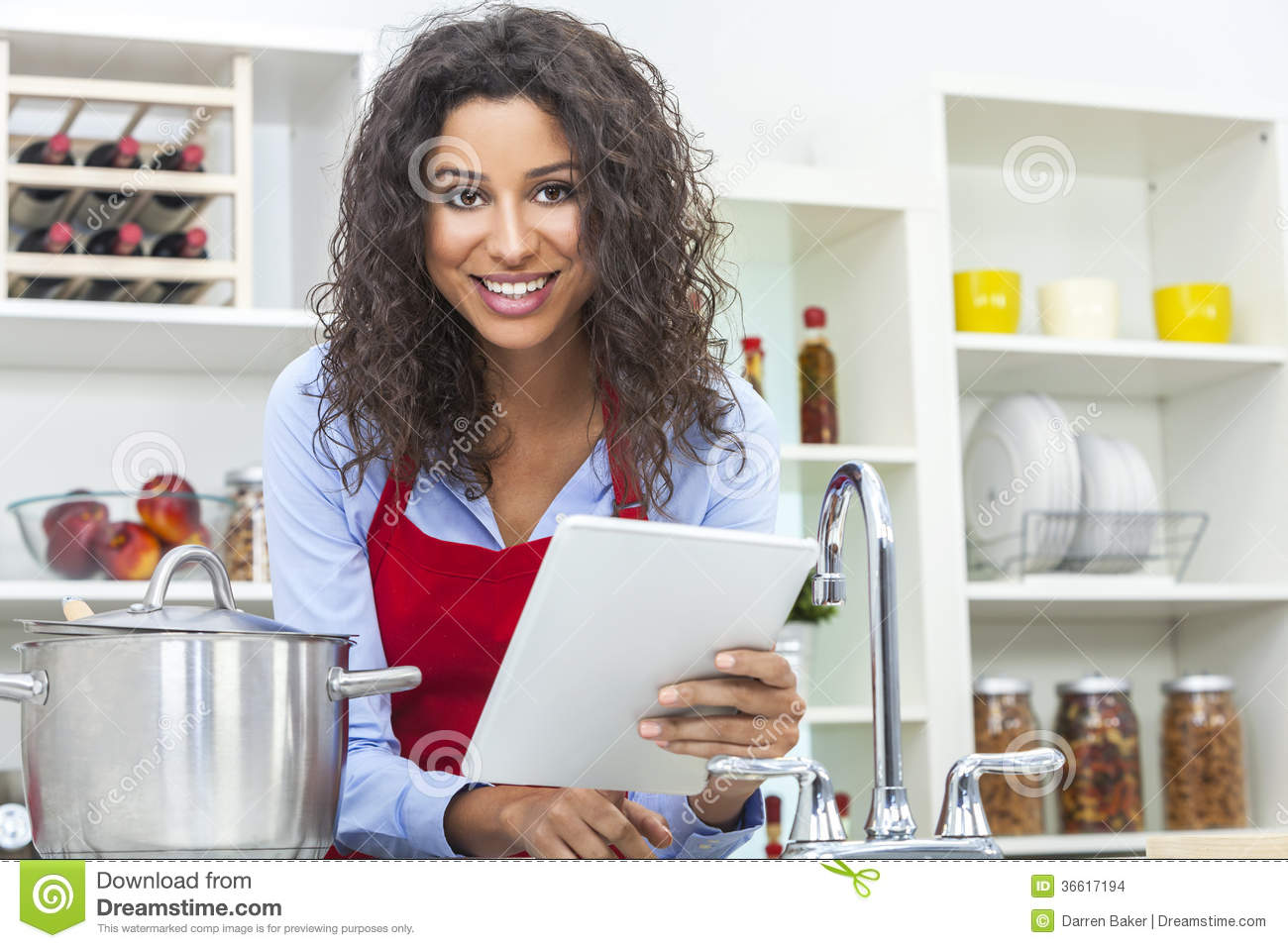 Woman Using Tablet Computer Cooking In Kitchen Stock ...