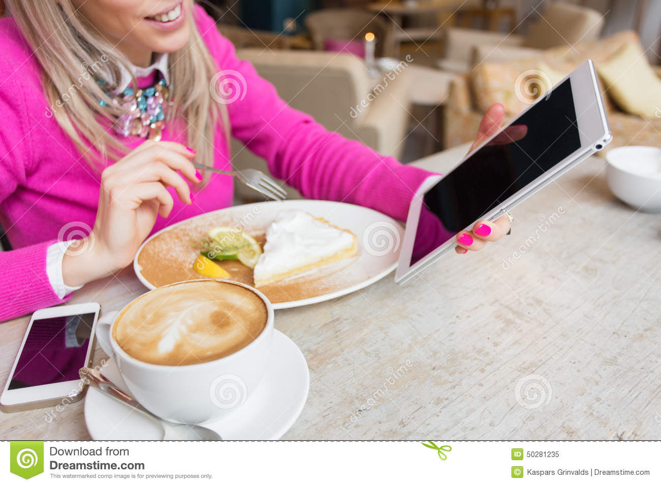 Woman using tablet computer while having cake and coffee in cafe