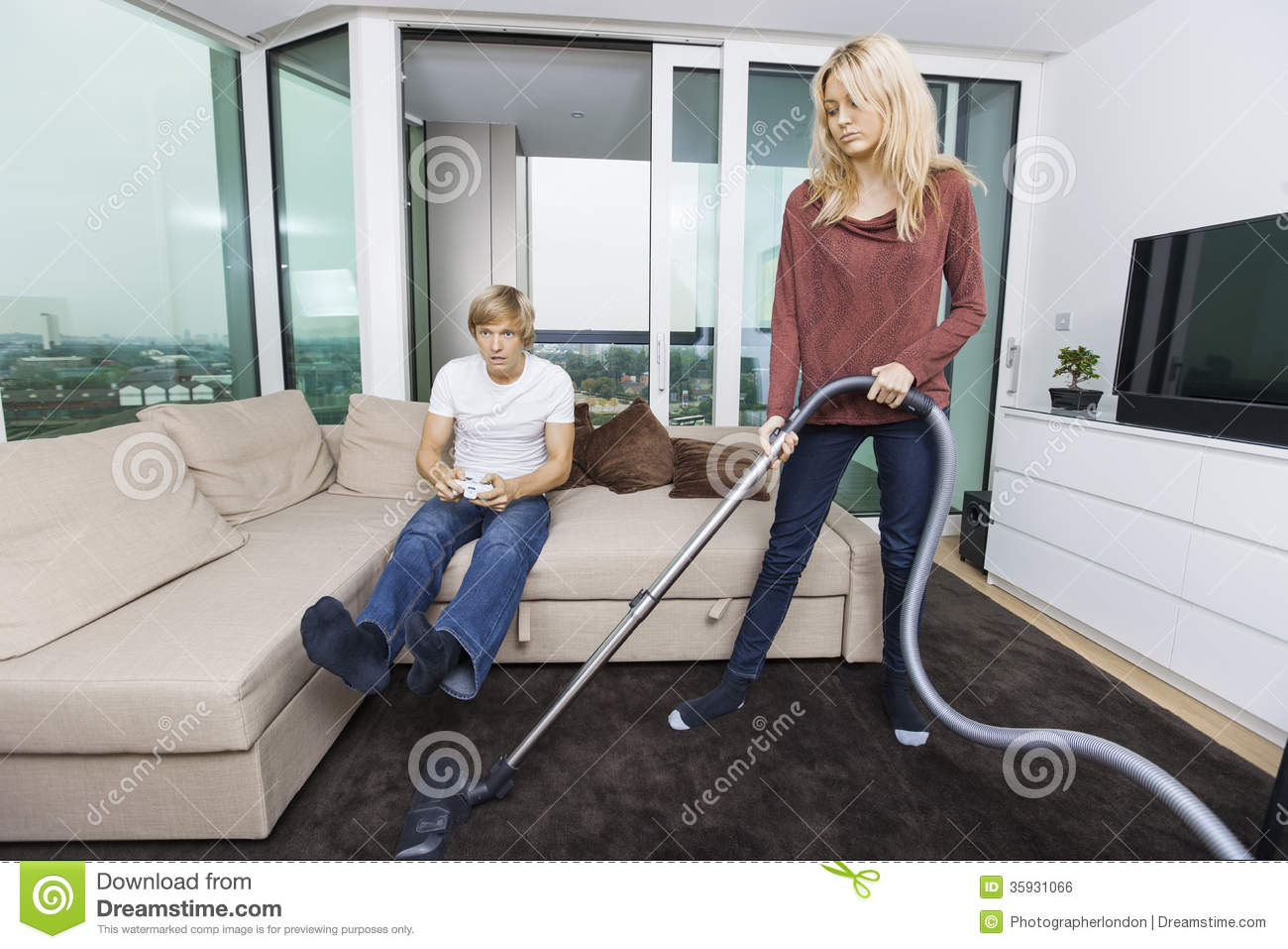 Man Living Room Woman Vacuuming While Man Play Video Game In Living Room At Home
