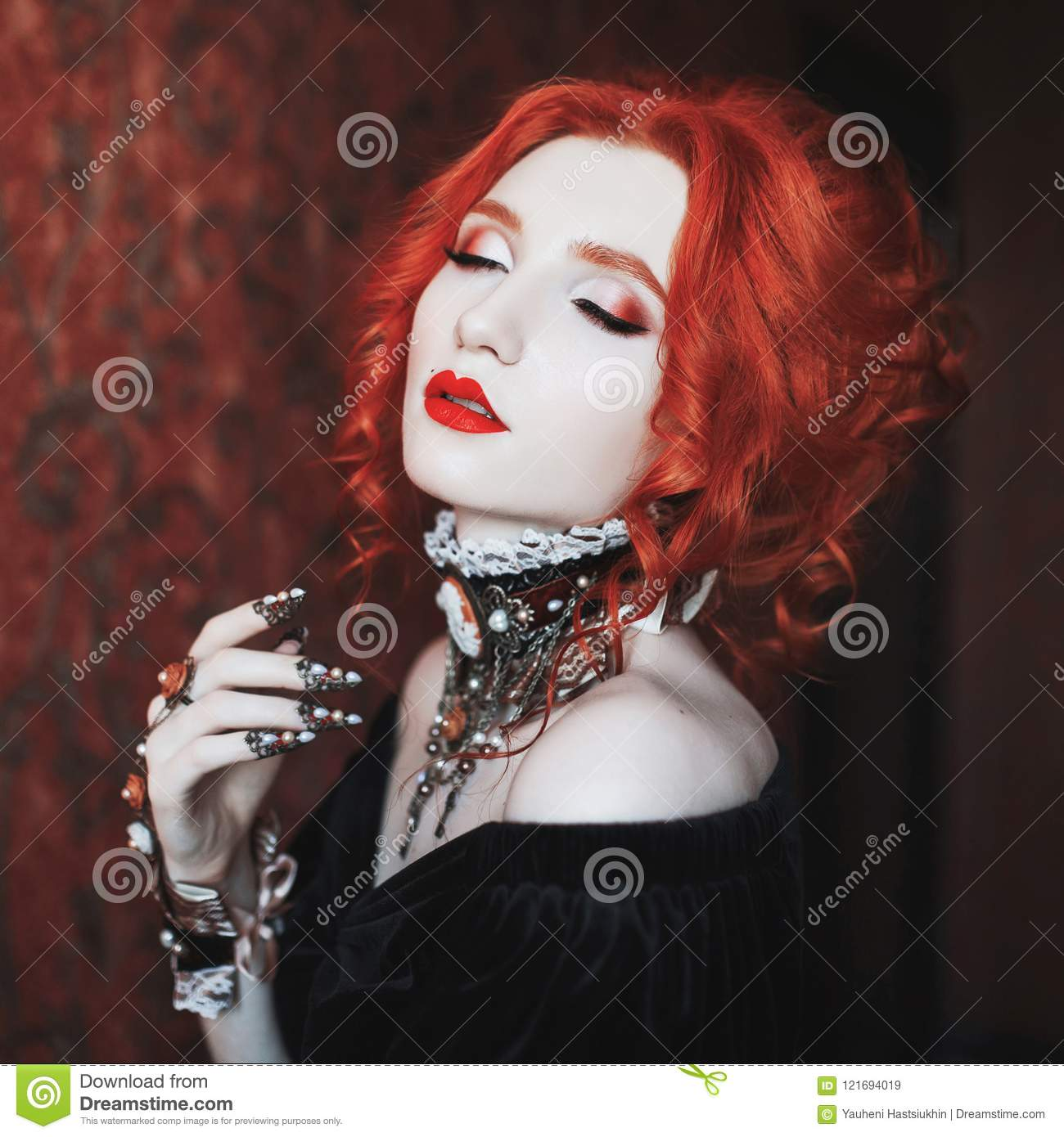 A woman is a vampire with pale skin and red hair in a black dress and a necklace on her neck. Girl witch with vampire claws