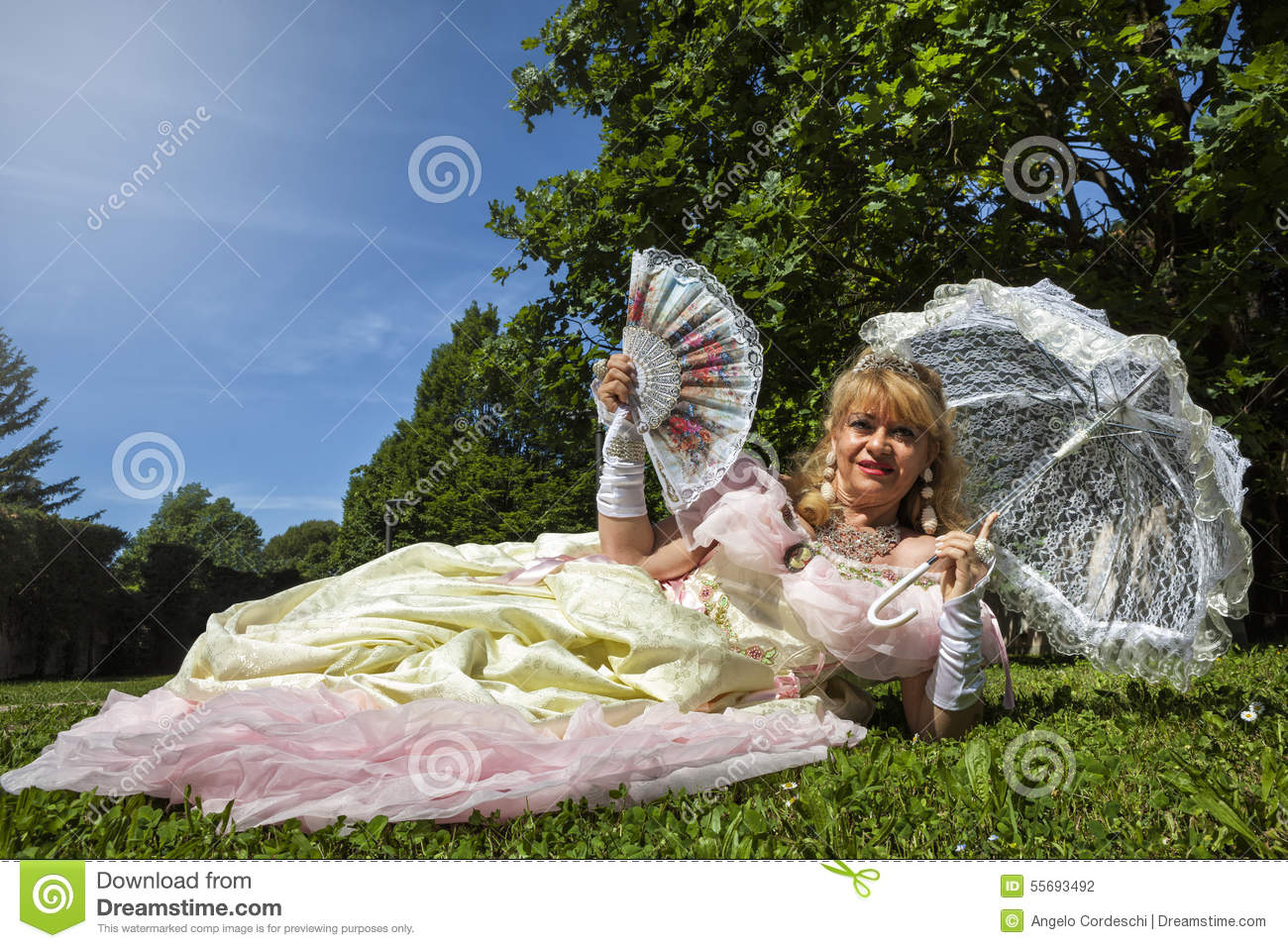 Woman in Venetian costume lying on the green park with white umbrella