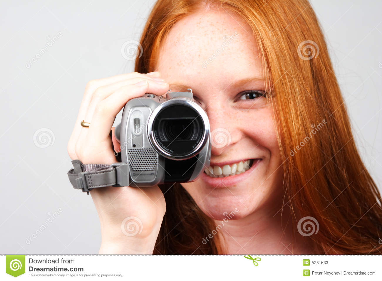 A young woman shooting video with an amateur camera on plain background -  closeup image. 6ee5edfebf