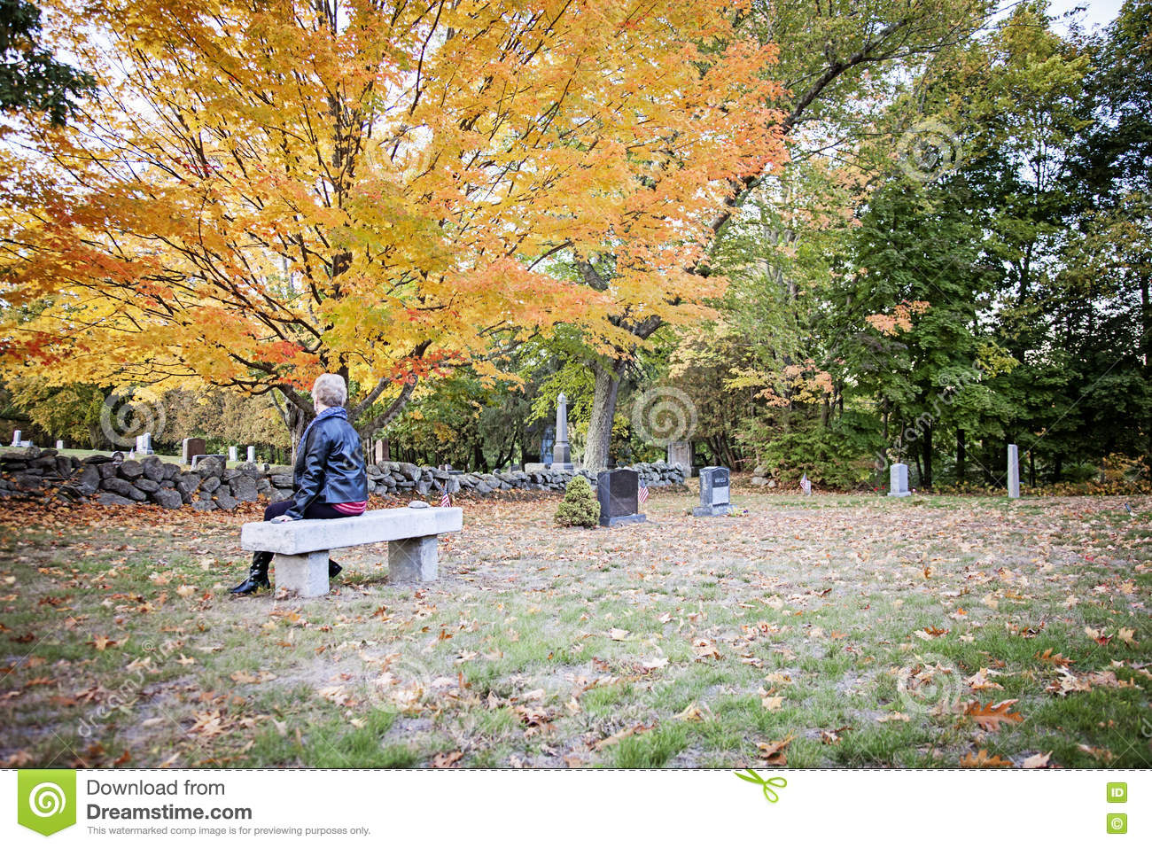 Woman visiting grave in cemetery