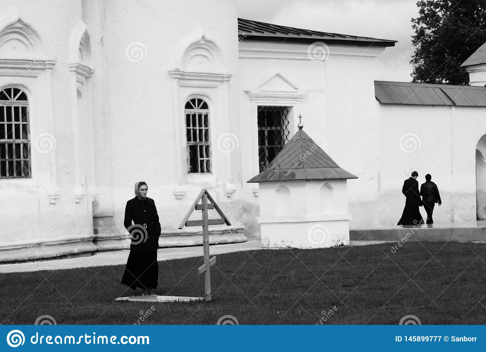 Tobolsk, Russia, 10/05/2016: A woman visits the grave in a monastery. In the background are the priests. Black and white