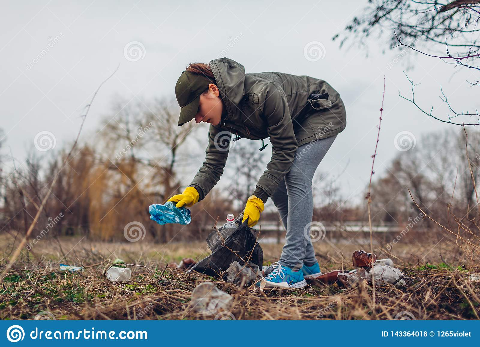 Woman Volunteer Cleaning Up The Trash In Park  Picking Up Litter