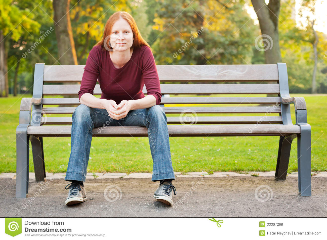 a woman waiting on a bench in a park royalty free stock