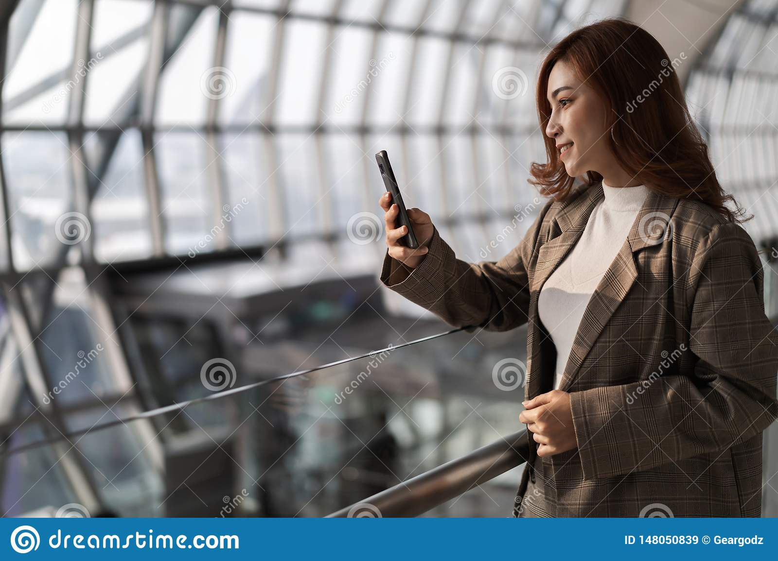 woman waiting for flight and using smart phone in airport