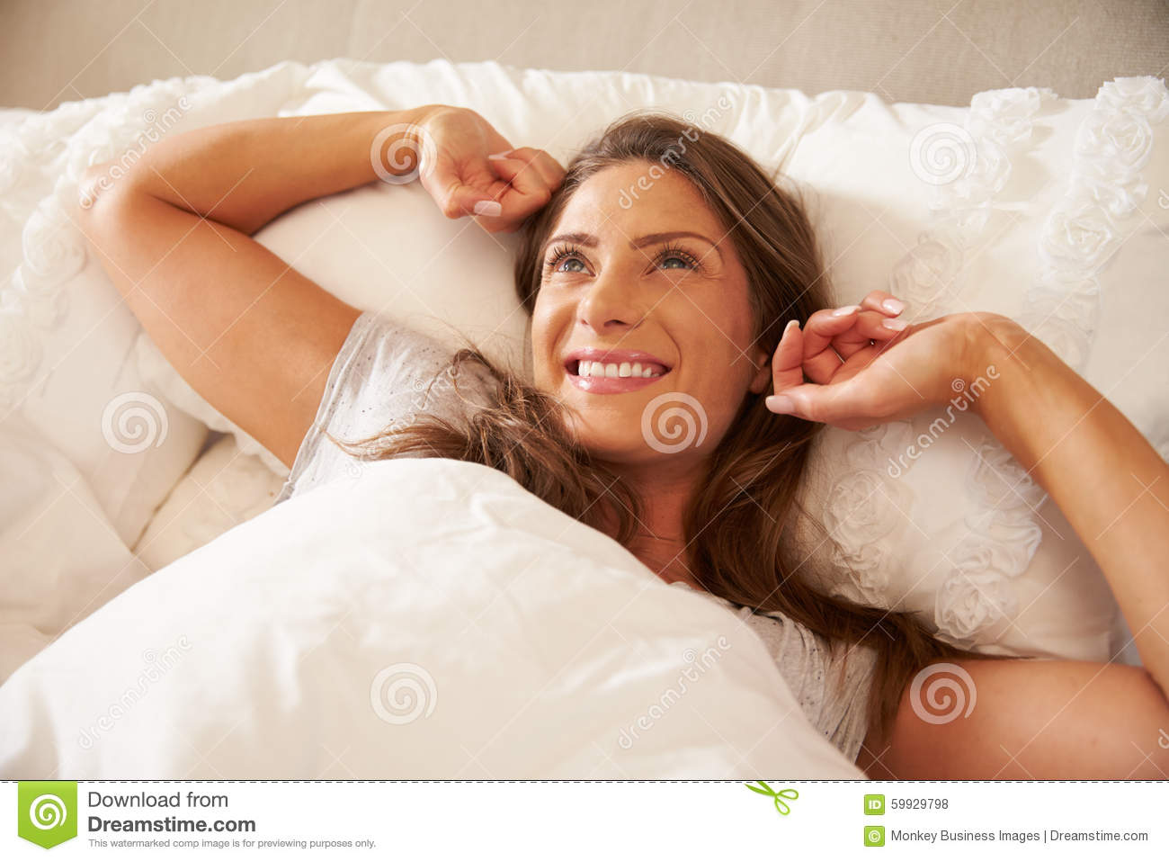 Woman Waking Up And Stretching In Bed At Home