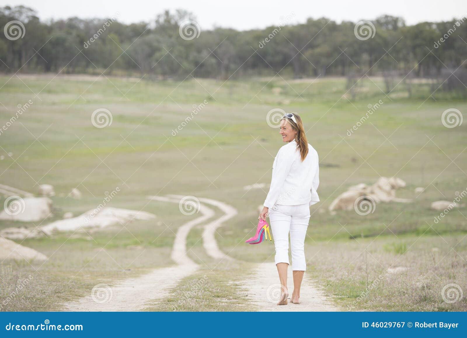 woman walking bare feet outdoor holding high heels stock image