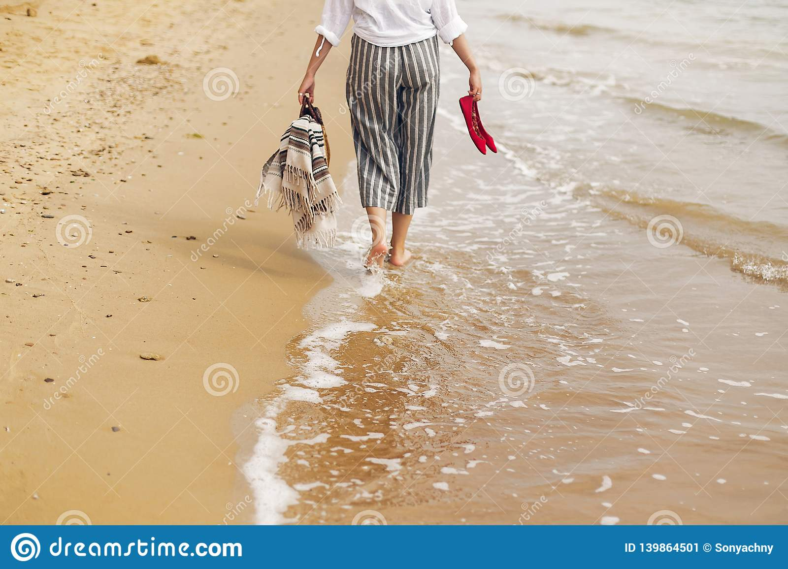 Woman walking barefoot on beach, back view of legs. Young girl relaxing on sandy beach, walking with shoes and bag in hands.