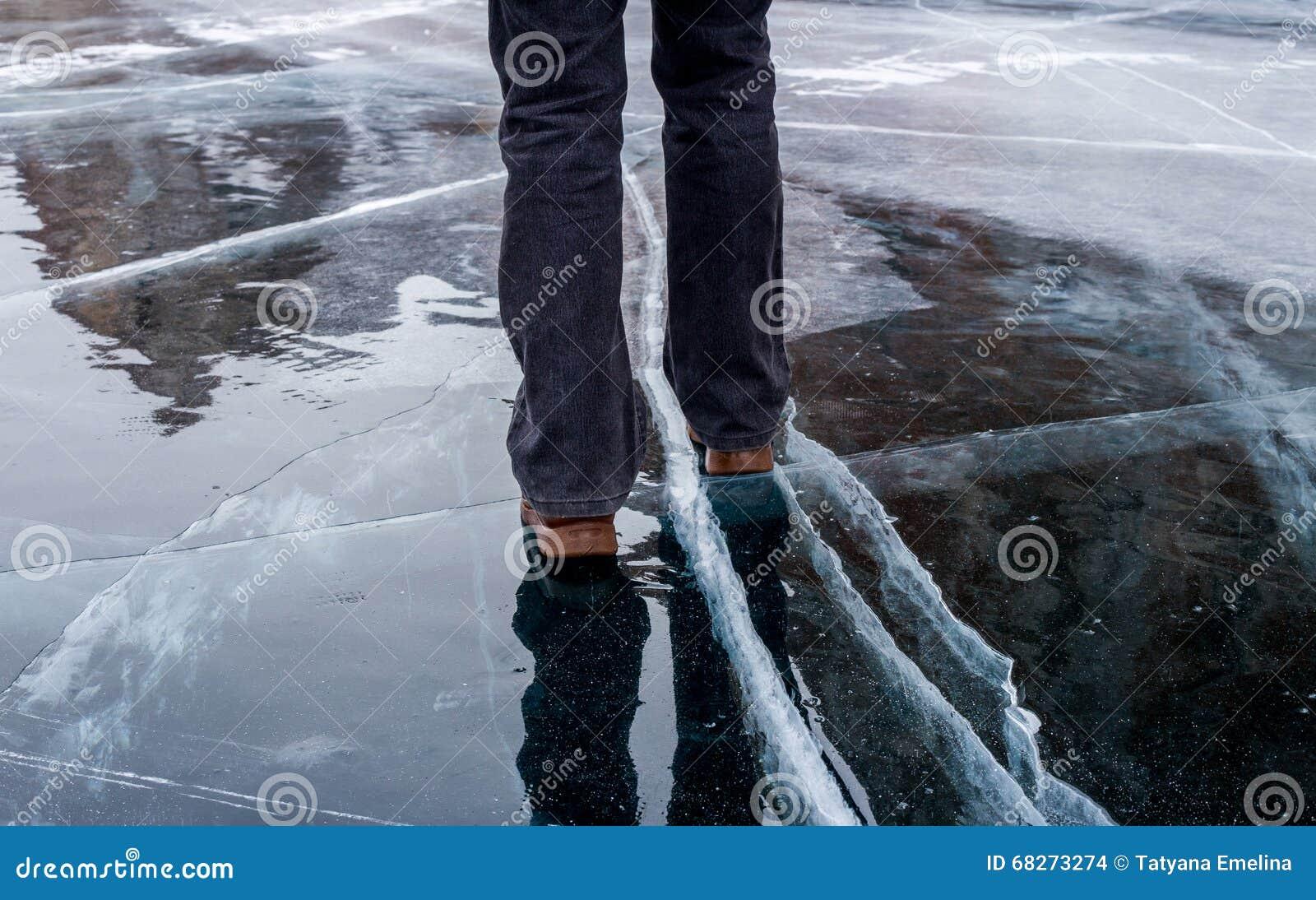 Woman walking on blue cracked ice of frozen lake Baikal.