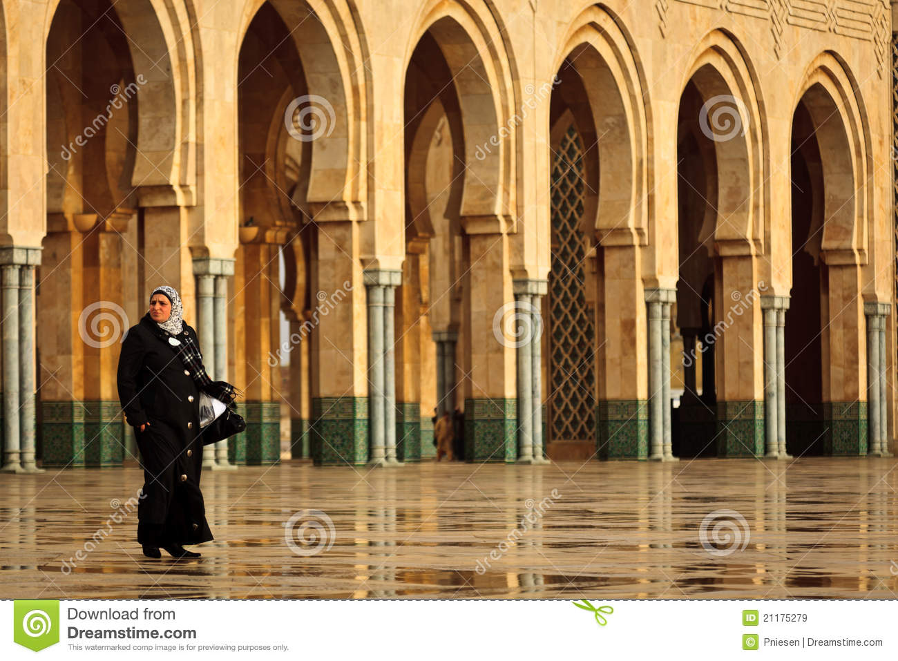 Woman walking in front of arches at mosque