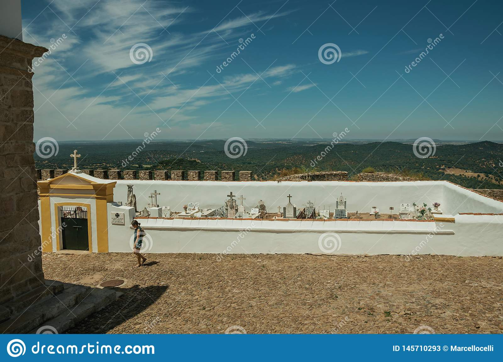 Woman walking in front of cemetery at Evoramonte
